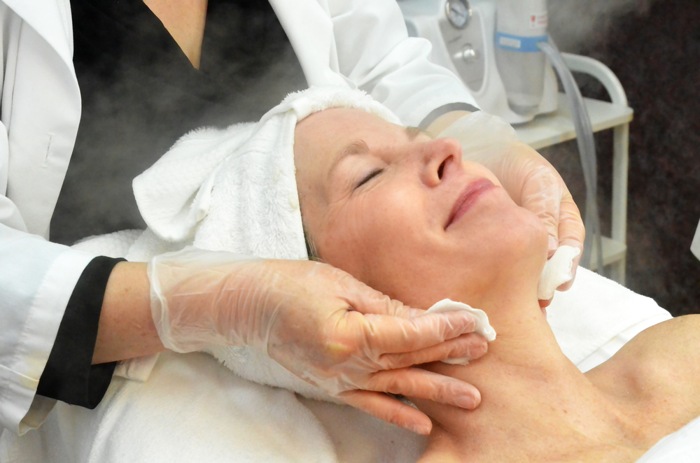 A client looks happy and relaxed while receiving a steam treatment during a rejuvenating facial