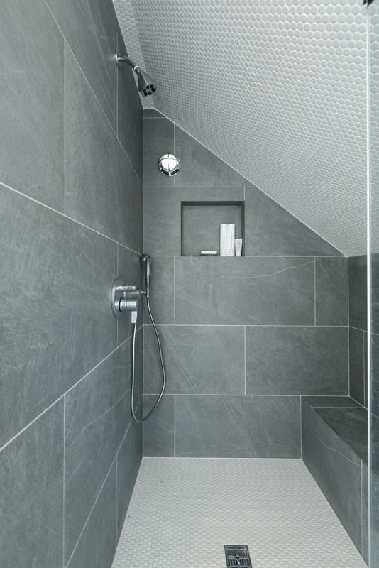 The unconventional shape of the shower was playfully accentuated by mirroring the floor and ceiling using white round tiles. The Hansgrohe dual-showerheads have an integrated push-button volume control, that mimics the (space)-ship-like ambiance of this whimsical space. The custom-built Carrara marble walls have a built in square shelf that contrasts the adjacent portal-shaped light fixture.