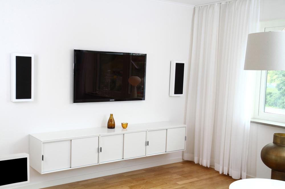Sie sehen hier 2 DLS OnWall Lautsprecher Serie Flatbox Large in weiß mit Subwoofer der an die Wand montiert ist. Schlicht, klassisch, einfach elegant.