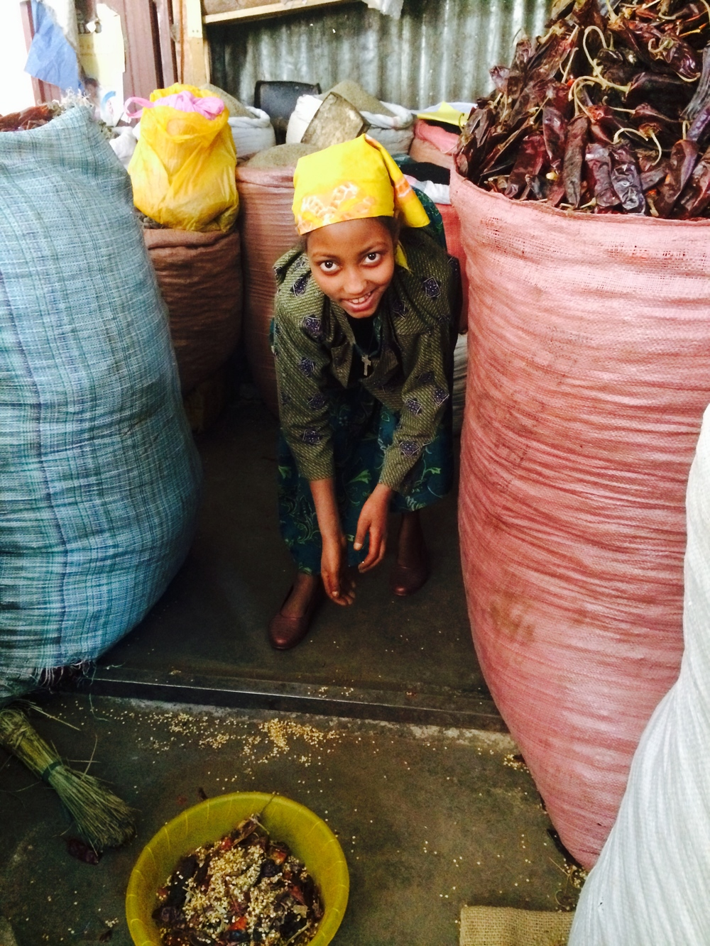 A young girl cleans up after her relatives cut the tops off of the berbere peppers.