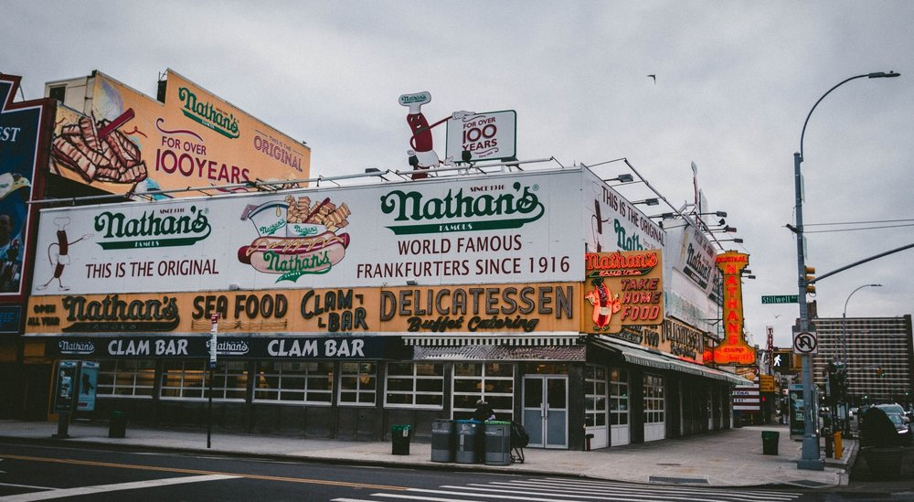 "Every Fourth of July, thousands of bystanders flock to Coney Island to watch the Nathan's Famous Hot Dog Eating Contest. The premise is simple—who can eat the most of Nathan's hot dogs in 10 minutes?  Part eating contest, part marketing strategy, and part tradition, the competition harked back to the brand's invention more than 100 years ago. In 1916, founder Nathan Handwerker opened his first hot dog stand on Coney Island, starting an empire that would eventually reach millions of customers across the country and around the world. Handwerker sold his hot dogs for five cents apiece—half the price of his competitor and former employer Feltman's—and soon gained a reputation for offering inexpensive, delicious food. According to urban legend, the Hot Dog Eating Contest began that same year on July 4, when four immigrants challenged each other to eat as many Nathan's hot dogs as possible to prove who was the most patriotic (the alleged winner, James Mullen, scarfed down 13 hot dogs in 12 minutes).  Nathan's started with hot dogs based on a family recipe but has since expanded its offerings to include hot dog buns, as well as fixings like pickles, onion rings, and chili topping and sides like its famous crinkle-cut French fries. The early years attracted the attention of celebrities such as Al Capone and Clara Bow and presidents like Franklin Delano Roosevelt. The expansion was reasonably slow, but a clam bar, full-service restaurants, and a booming franchise operation developed in the second half of the twentieth century. Today, Nathan's products are found in local grocery stores, as well as dedicated Nathan's restaurants, and concession stands in major cities across the U.S.   Nathan's brand recognition is such that the name is synonymous with words like ""hot dog,"" ""crinkle-cut""—and even ""America."" In 1939, FDR brought Nathan's famous hot dogs to the King and Queen of England as an act of patriotism. In 2017, Nathan's earned the distinction of being the ""first official hot dog"" of Major League Baseball, America's national pastime. And every Fourth of July since 1972, the Hot Dog Eating Contest has been televised on ESPN.  Despite its widespread success, Nathan's has not forgotten its humble origins. The original Nathan's restaurant remains in the same spot at the corner of Surf and Stillwell on Coney Island – and still hosts the annual Hot Dog Eating Contest a century after its founding."