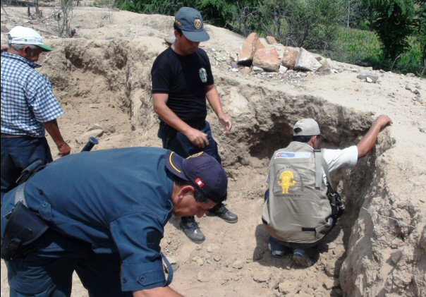 Peruvian police and volunteers inspecting  huaqueros ' handiwork.