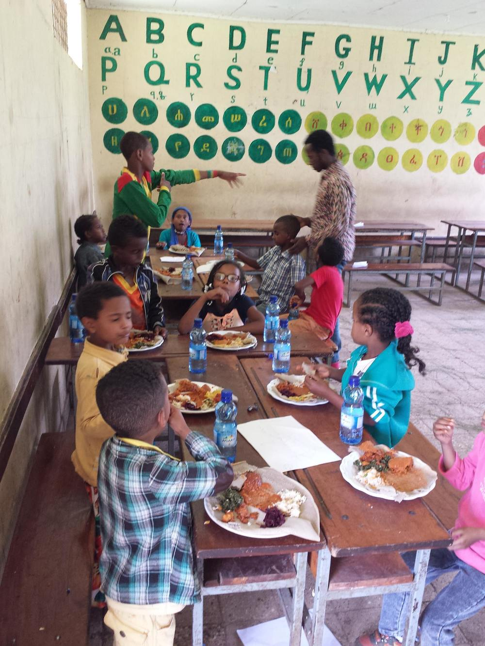 Deaf youth enjoying lunch at a special summer program organized in partnership with Visions Global Empowerment & their volunteers from USA.