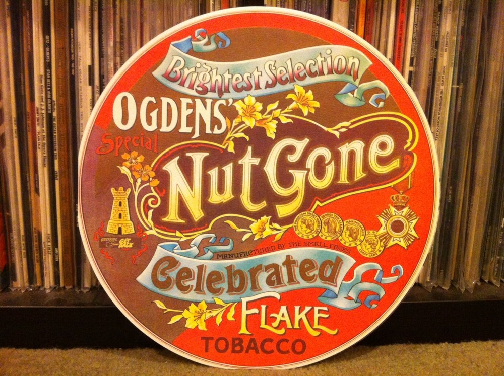 "The Small Faces Bask In The Afterglow Of Ogdens' Nut Gone Flake!!!    The Small Faces. Four well-dressed diminutive mods in search of a proper psychedelic album found their Holy Grail in between the grooves of a long player that landed on God's Earth in 1968. Of course it's called Ogdens' Nut Gone Flake. Why not?   This heavily played record is a basher. It's unlike any other I've heard in the genre. Excellent musicianship, interesting production, hilarious East End accents (""Ello Mrs. Jones, ow's your Bert's lumbago?"") and a kind of self-parody come together to punch you in the kidneys after tickling your toesies.   The bulk of what is called ""psychedelic music"" is often overly serious and occasionally too self-aware. The first bit of this record – the opening instrumental title track in particular – might fool you into thinking you're in for a pretentious festival of swirling guitars and echoing organ runs. You'd be forgiven for thinking something like that, but it is a great cut. But it's the next track – Afterglow (Of Your Love) – that will set you straight for the rest of the record. Mostly. It starts with some hand clapping, East End mumbling, bongos and acoustic guitar before descending into a heavy Motown-fueled soulful punch of overcranked musicianship that feels like the older, tougher brother of another, earlier Small Faces winner called ""All Or Nothing."" And that's not nothing, my friends. Strong medicine indeed.   More hand claps and heavily echoed organ kick off the next track – Long Agos And World's Apart – which serves as a romping bridge to the next song – Rene. Pronounced ""Reeney"" by a mugging, winking Steve Marriott, this one's a song and a half really. It's the story of Rene – the docker's delight – and it reminds me of the kind of old-timey fishermans' songs until it kicks into an instrumental psychedelic freakout. Which is a good thing because it works. Probably because Ronnie Lane, Kenney Jones, Ian McLagan and Steve Marriott manage not to overthink their brand of psychedelic. Song Of A Baker then pulls itself up by it's flour and water and forms itself into a quite a pie indeed. The last cut on the A side of this long player is Lazy Sunday. Hilarious. Even more so because it was written as a joke and accidentally (?) released by Immediate Records as a single (to Mr. Marriott's great displeasure). But like so many tales of pop groups and record labels, the joke managed to be on everyone. Lazy Sunday became a number 2 hit in Great Britain.    Flip this long-player over. But not before preparing yourself. Suck down a pint of your favorite ale, tickle the wife and scream out the window to clear your pipes. It's on side two where this business of not taking psychedelia too serious gets down to business. It's all about some Cockney cat named Happiness Stan – narrated throughout by a real Stan – Stanley Unwin. I don't know where the Small Faces found this guy but man is he freaky. Funny too. Speaks nonsense to my ears but I can't be sure. He's probably some Lord of Hamburger-Wolverhampton. Rollin' Over is the second track and it's worth the wait. Heavy bit of flash, this one is. A few more dollops of psych follow in the form of The Hungry Intruder (a light moment), The Journey (silly stuff really), and Mad John (great vocals by Mr. Marriott!). The record finishes with Happy Days Toy Town – a song that shockingly reveals the meaning of life through the opening line ""Life is just a bowl of All-Bran!"" It's a downhill giggle the rest of the way, love.   And, that's it exactly. The Small Faces introduce us to a giggle of a psych album that somehow manages to rock hard enough to keep your toe tapping and give you something to think about. Sure keeps your mind off the war in Indo-China.       Listen to Afterglow (Of Your Love) by clicking this very sentence!!!        For weirdos only:  The record pictured above is a Get Back label reissue of the original 1968 LP. Good luck finding a clean original! The package ripped off a brand of tobacco called Ogdens' Nut-Brown Flake. The cheek! Some guy named Mick Swan designed the cover. Nice work, Mick! Ogdens' was the last studio record of new material by this line-up. Not long after it's release, Steve Marriott jumped into a band called Humble Pie with future talk-box weirdo Peter Frampton. But in these early days Humble Pie were an authentic blues-rock group worthy of their name. The hole left in the Small Faces was filled by two well-known rockers – Rod Stewart and Ronnie Wood. They cut one LP as The Small Faces and then dropped the ""Small"" after realizing Ronnie was a hair over 5'6"" tall with the right haircut. God bless his socks."