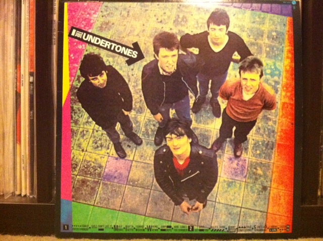 "The Undertones. Derry Singles Farmers.    The most pop punk band from Derry, Northern Ireland? The punkest pop band? Can there be any doubt? Admittedly, I've never tooled around Derry's sectarian streets looking for a better band. But I'll venture a guess that there'll never be another single cranking machine from up there who's any better.  Have a look for yourself. Bear in mind they'd spot a poser like you in a flash and box your ears.   This short canary cage liner of an article will explore my fascination with the first Undertones long player. A gift from God to the world from guitarist bruvvers Damian and John O'Neill, bassist Michael Bradley, Billy Doherty on the sticks and a concave-chested  gent named Feargal Sharkey on lead warble. I once said Mr. Sharkey was the poor man's Bryan Ferry and nearly got punched in the mouth. I stand by it as long as the goons are gone. Sure, one's more of a quivverer and the other a warbler. But still, nobody knows how either of 'em does it.   Let's get into the thick of it. First off, the record you see above is the second pressing of the band's first LP released on Sire Records. God bless you Seymour Stein (the Sire Records genius responsible for signing The Ramones, The Dead Boys, The Flamin' Groovies and on and on.). I guess he signed them to Sire because ""they got sawngs."" You see, Seymour loves bands that have songs.  More on that another day. My copy came out in October 1979 and has two front covers. Sort of. You can flip it and both sides have a cover photo. Either that or no back cover. My head hurts thinking about it. Most import, however, is the fact that the October '79 copy has two additional tracks including a real life saver – Teenage Kicks!   Teenage Kicks is the best single ever recorded according to John Peel. It was the BBC radio impresario's favorite song until his untimely death a few years back. Think about it. Of all the songs John Peel heard in his life, he considered Teenage Kicks the ultimate. The numero uno. Boggles the mind. Makes me want to wolf a Mars bar right now!   But this album is packed with singles even if they weren't released as such. In addition to the two listed above, you gotta love the sweet surround of songs coming at you on this record – Family Entertainment, Girls Don't Like It, Male Model (!!!), I Gotta Getta, Jimmy Jimmy, Here Comes The Summer, and more! My guess is you're not going to find too many records from 1979 with as many two minute masterpieces! If you do, prove it. Tell me about it. I want to hear it.     Click this sentence for proof that John Peel is right about Teenage Kicks .     For weirdos only: The first pressing of this record came out a few months earlier – May 1979 – and has a black and white photo of the band. Here's a case where it's better not to be the early bird. The second pressing has the first beat by two full songs – Teenage Kicks and Get Over You. Two serious singles, m'friend! Curiously, the October pressing sports a re-recorded version of Here Comes The Summer. Not sure why. Both versions are very similar. I know because I have a compact disc (blasphemer!) reissue of the album with all kinds of bonus tracks. Worth it, punters."
