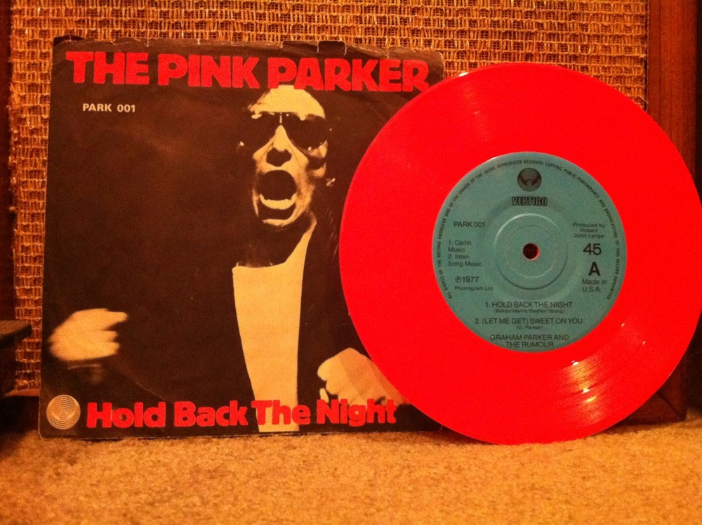"Think Pink, Parker!!!    Hey, with only four songs this story should be shorter than the stories I write about LPs right? We'll see. I may not have enough time to  make  it shorter.   The Pink Parker. On Vertigo. An E.P. -  Extended Play  for the uninitiated. Four cuts. With The Rumour backing him up to the wall! This record sounds like it was recorded under a tall table in the corner of a North London pub filled with smoke, sweat and at least two guys named Ivor looking to pound you into the ground after downing nine ciders - before the show starts. And, I'm just describing the two studio cuts - Hold Back The Night (by The Trammps!!) and (Let Me Get) Sweet On You. The other two cuts are recorded live and this nifty little EP says they're taken from the hideously rare ""Live at Marble Arch"" bootleg album. How 'bout that? Beating the bootleggers at their own game. The cheek! The live cuts? Sizzling versions of White Honey and Soul Shoes from the very first Graham Parker and The Rumour long player - Howlin' Wind. My six year old daughter heard these live tracks this morning before school and said ""This sounds awesome!"" Which it does.    The Rumour? Pub rockers extraordinaire. I'm talking about Brinsley Schwarz (g; and formerly of the band Brinsley Schwarz with Nick Lowe, et.al.), Andrew Bodnar (b), Stephen Goulding (d), Martin Belmont (g) and Bob Andrews (k; and also formerly of The Brinsleys).   But it's, Graham Parker on lead sneer all the way. Doing what he could to anticipate Elvis Costello's sneer and one-up it  before  Costello even cut an album. Talk about foresight! True, they're a goofy looking lot but they know how to rock.    If you click this sentence you'll see the proof!     For weirdos only:  Graham Parker thanks Brian Robertson of ""Thin Lizzy's"" on the sparse liner notes on this slab of pink wax. I have no idea why. Do you know? And, if you were wondering where Graham Parker's been hiding since the early 80s, I know. In the $1.00 bins at America's local record shops. I see his albums constantly hiding out under the full price records. If I were you, I'd  get down on my knees and start digging in the P section because they're usually in great condition and cost a buck. No kiddin'. I bought this E.P. earlier this week for exactly 49¢. Special thanks to Spindlephonic Alan for reintroducing me to the merits of Mr. Parker and friends."