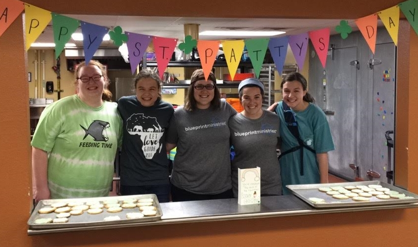 (From left to right) Abby, Janae, Taylor, Abby, and Hope serve a St. Patrick's Day treat to our spring break campers.
