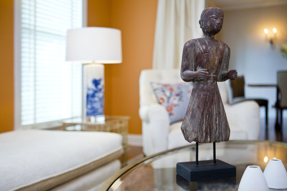 Global antique statuette on metal and glass table. Bright linen upholstered chaise lounge and chair fill the rest of the room. Tangerine walls liven the transitional room.