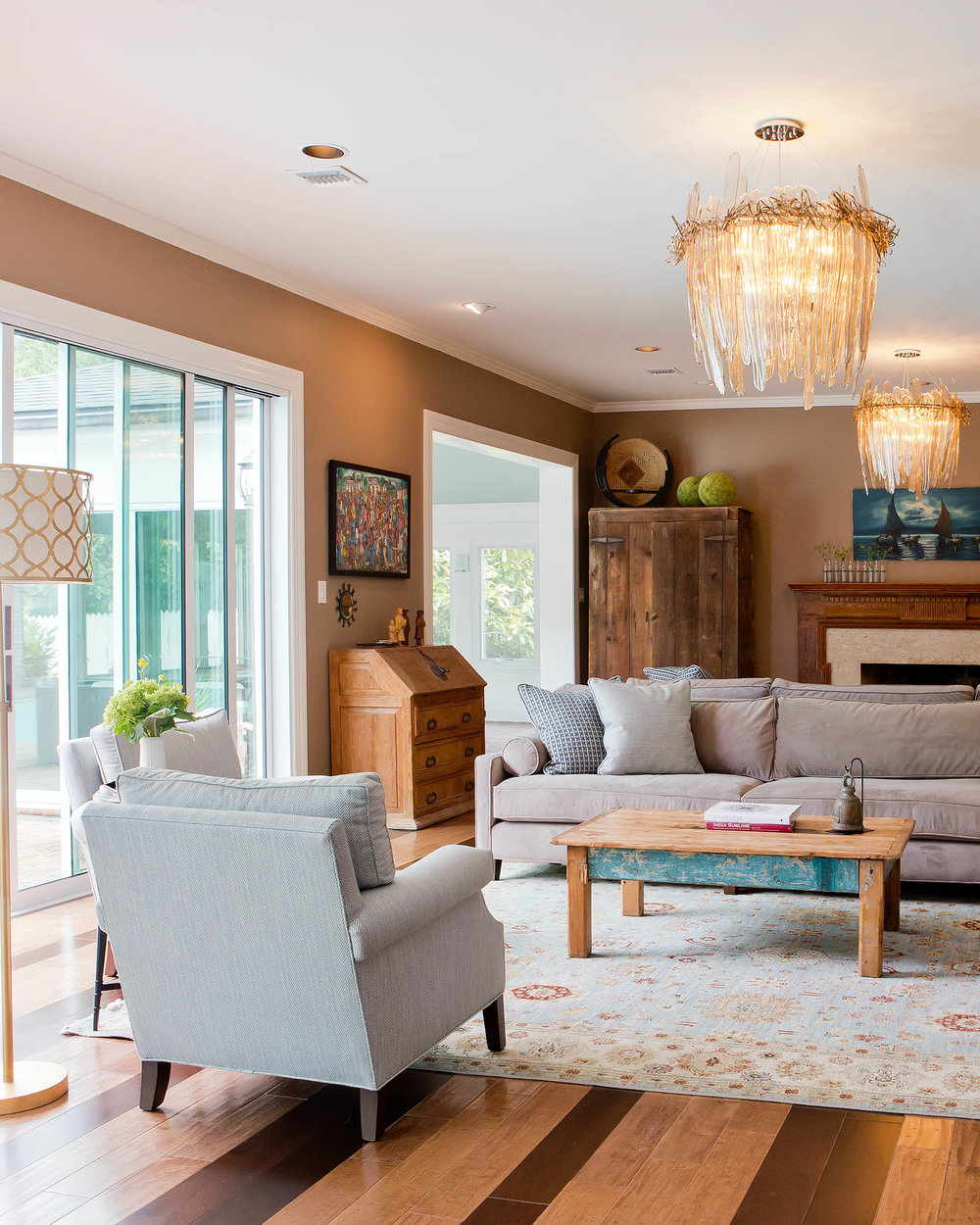 Traditional rug in warm toned living room. Two chandeliers and large windows bring light into the transitional space.
