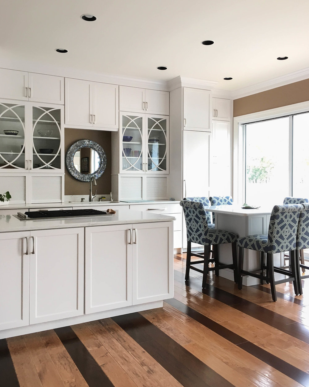 Beautiful striped floors in bright white kitchen with upholstered bar stools.