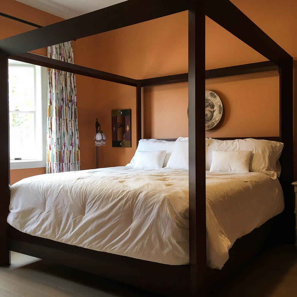 Four poster bed with crisp white sheets and dark orange walls.