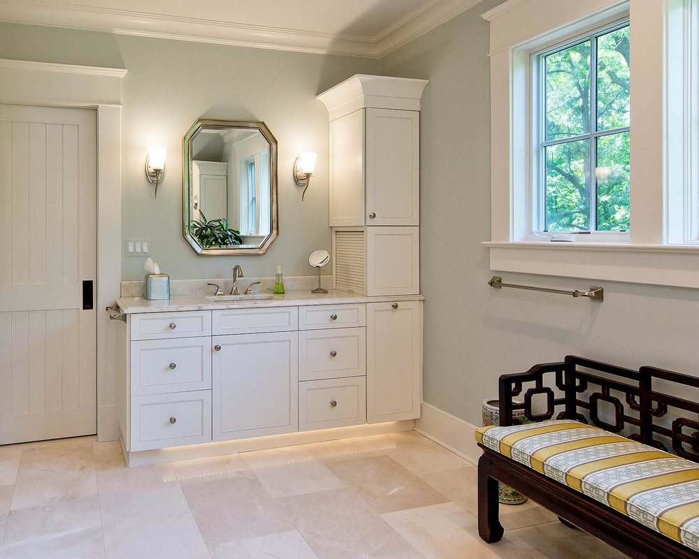 We designed unique custom touches in this bathroom in our client's home outside of Manassas, Virginia on the Potomac River. Quality tile and flooring finishes and under cabinet lighting add to the luxury. We used a family antique with a re-covered seat in a new designer fabric.