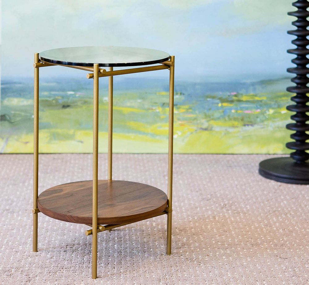 Our Katie drink table combines burnished gold, bronze glass, and natural walnut to embody a modern, organic elegance.