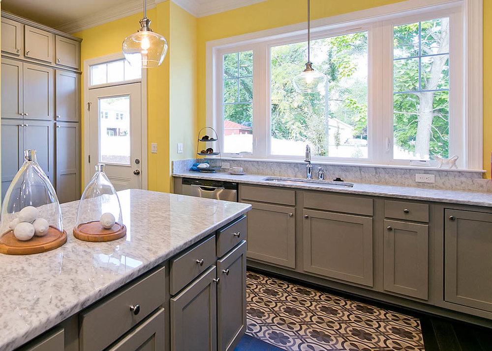 Spicher and Company vinyl floor cloths look like vintage painted oil cloth. Custom sunny kitchen design with grey cabinets and gray countertops. How to decorate kitchen countertops. Designer model home kitchen.