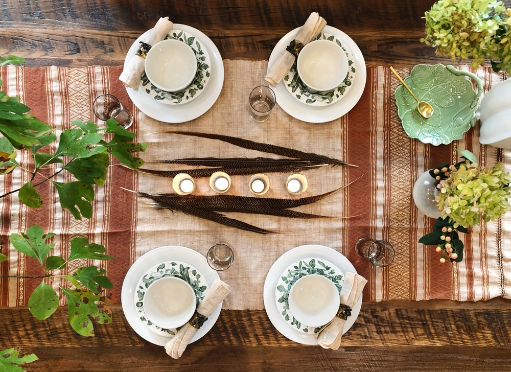 How to set a large table for four dinner party guests. Bunch your plants or use twigs and greenery at each end of a long table to fill up space and make friends feel cozy. This table scape shows you how to throw a dinner party for four people at a big American Made farm table.