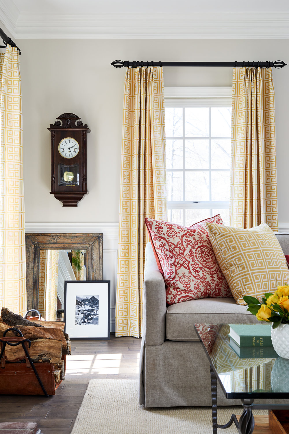 Gray slipcovered couch in farmhouse family room. Custom greek key curtains. Custom designed pillows for living room. Gray sofa and glass and metal table. New wide plank floors in classic colonial country house. Photo by Stacy Zarin Goldberg