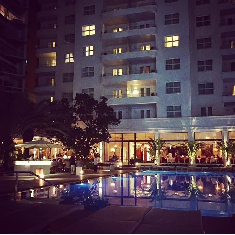 View of the pool at night from the outside bar tables