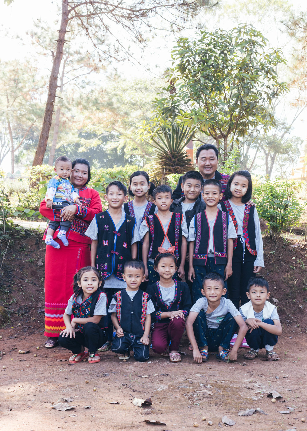 Group photo of a safe home in Tachileik, Myanmar. Each home consists of a pair of house parents and 10–12 children that are brought in from each area.