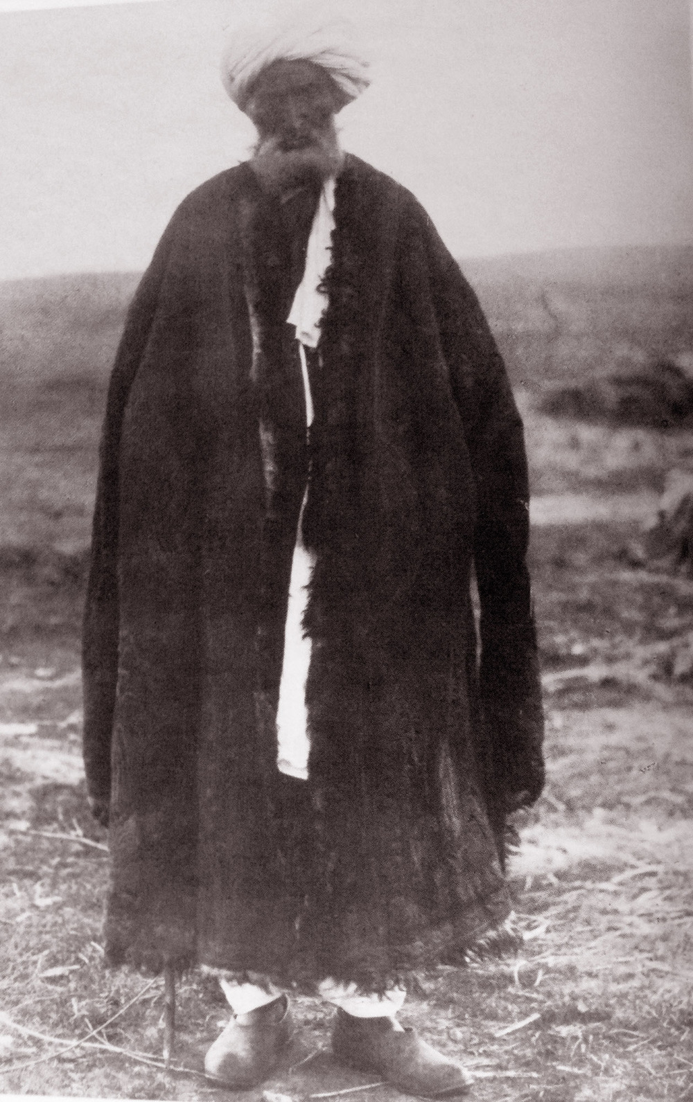 Hazara man sporting a well used coat similar in styling to the  Pashtun Skin Coat of 1867  called a posteen. The edge of this coat appears to be embroidered with a narrow band using the recumbent S motif repeated along it's length. The fur is facing inwards and the outside of this posteen is covered with a patterned fabric, the lining being made from karakol sheep skin.