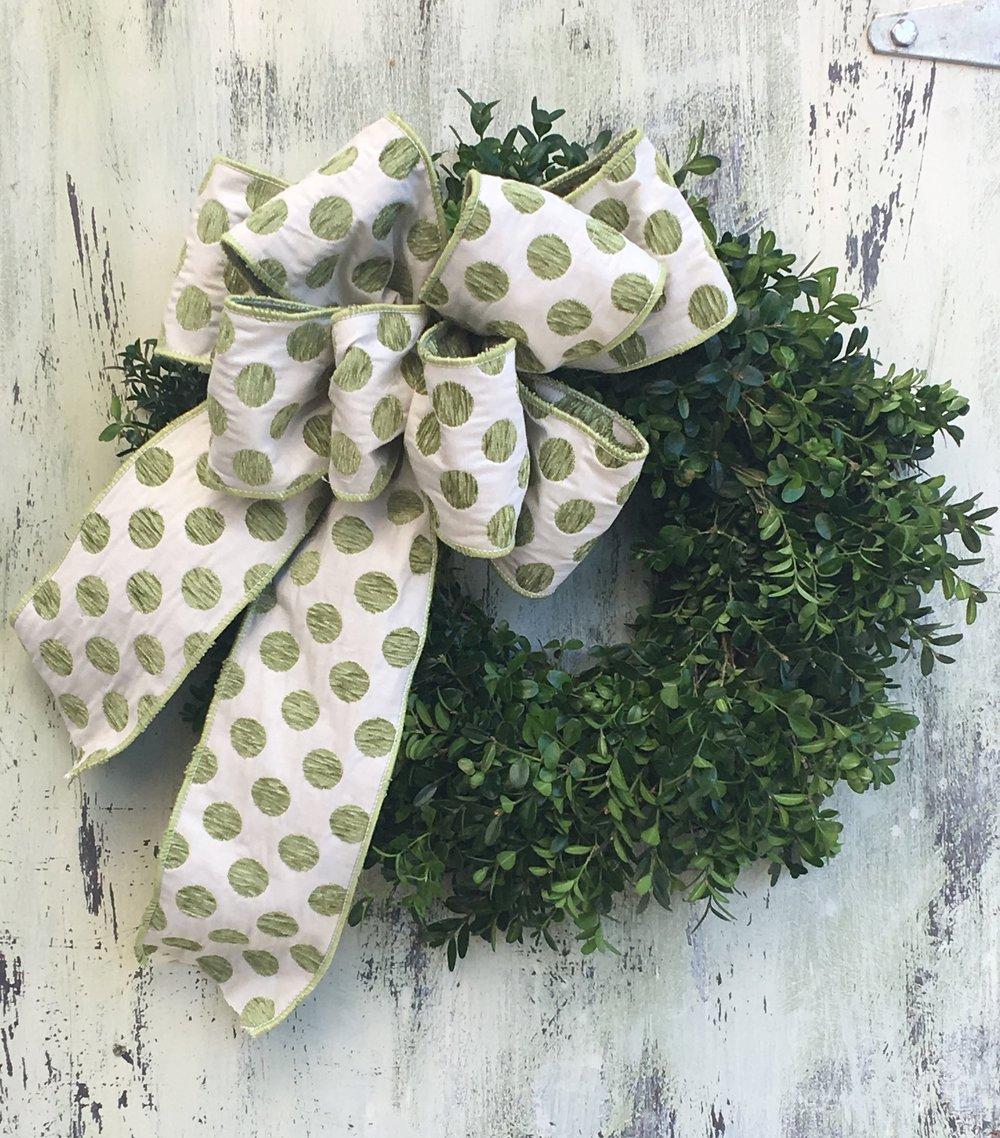 Whimsical polka dot ribbon on boxwood wreath.