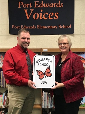 Mrs. McGrath presents Mr. Cronan a sign to be hung on the Elementary School celebrating the achievements of the school in helping to protect the Monarch Butterfly. Photo via  Port Edwards School District .