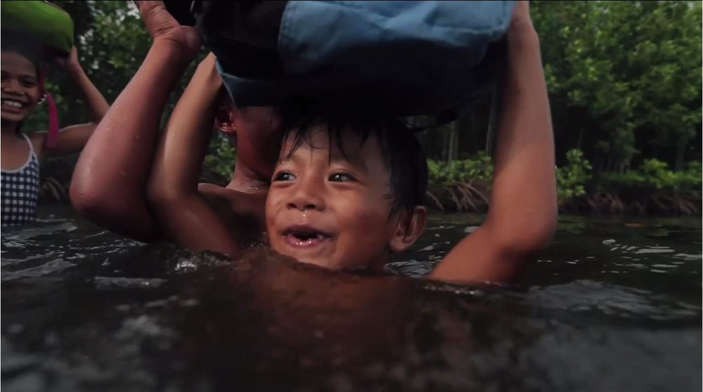 A child in Zamboanga wading through the water as he makes his way to school Source: Yellow Boat of Hope Facebook Page