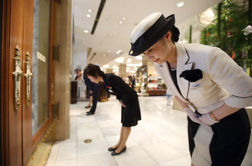 Store attendants welcome the first customers of the day as doors open at the Mitsukoshi department store in the Nihonbashi district of Tokyo, Japan.