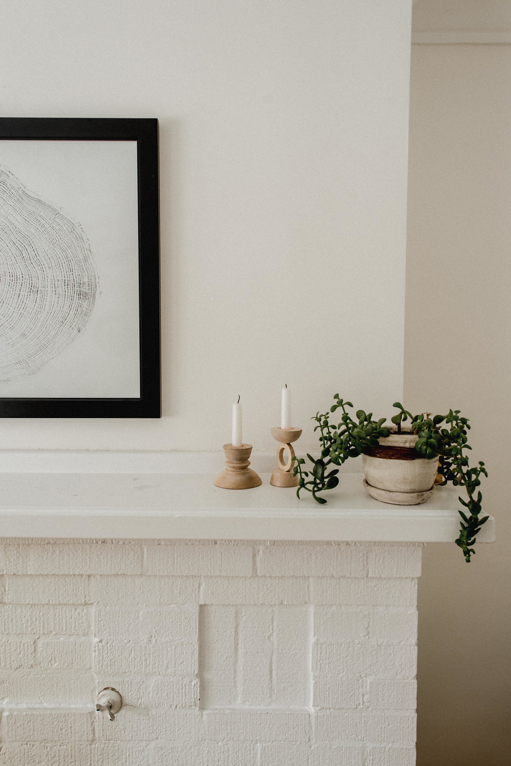 Simple mantle styling with plant and wood candle holders