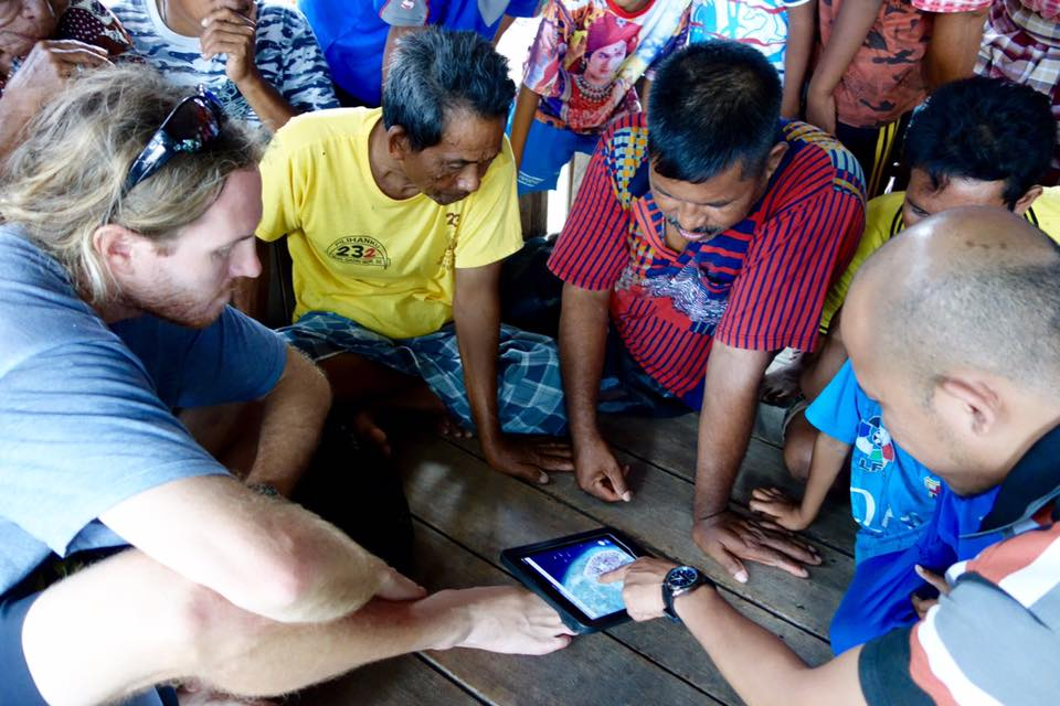 Austin asking fishers of Pulau Bontosua where they go to catch coral reef 'squid', or cuttlefish.