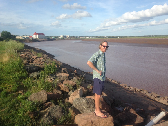 Austin stands along the Petitcodiac River in Moncton, NB, Canada. The river has an impressive tidal bore and chocolatey-brown color.  Photo credit: Celeste Venolia