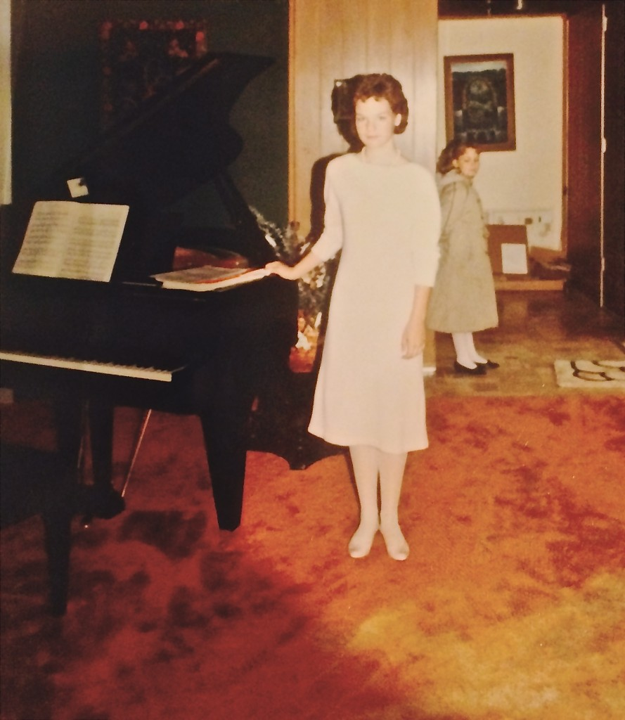 Freshman year (at home in our living room, with my sister Liana behind me), getting ready to accompany the Freshman Choir concert. Attention to solo piano playing already fading.