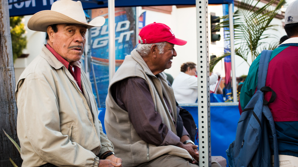 A Mexican man sits on the street, watching people pass by.