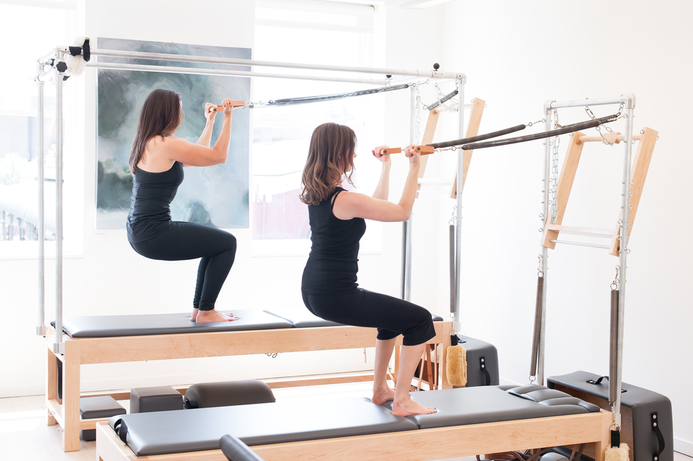 squats with arm springs on cadillac and tower pilates apparatus