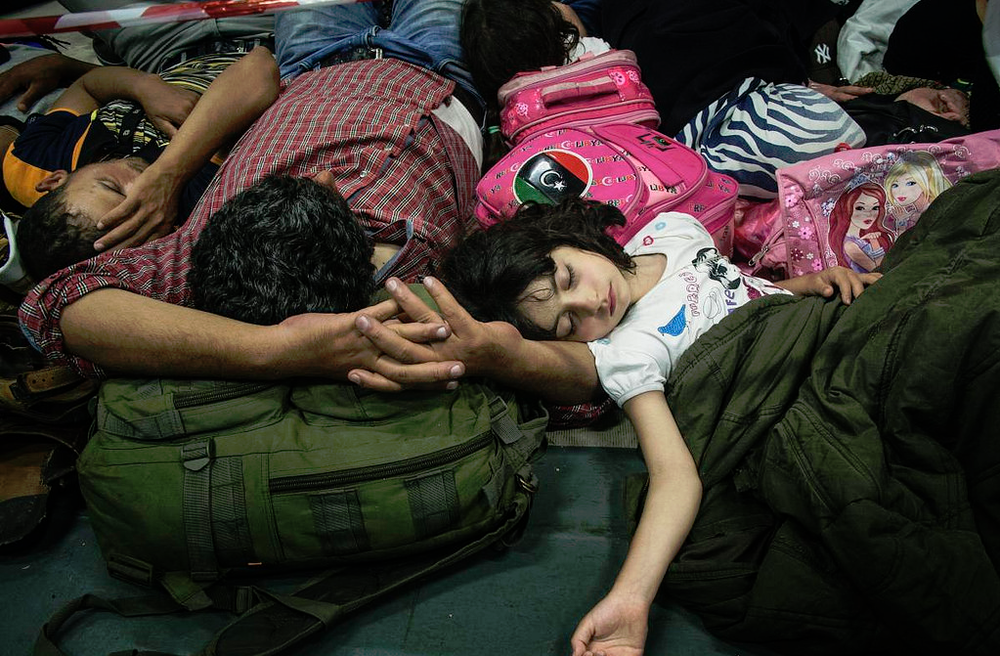 An exhausted Syrian family sleeps on an Italian Navy coastguard ship after being rescued from a fishing boat trying to cross the Mediterranean.