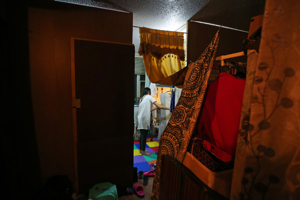 Xue Sun, a manicurist who uses the name Michelle, in the Flushing, Queens, apartment she shared with her cousin, Jing Ren, and four other people. Curtains separate the beds.