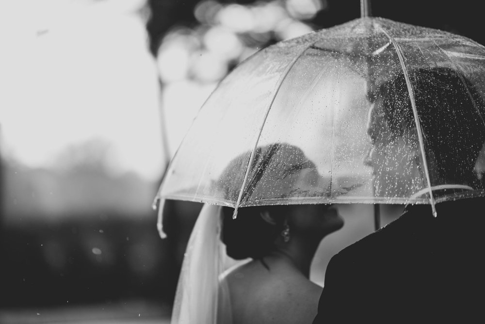 Bride and groom under an umbrella in the rain at Hudson Manor, Louisburg, NC