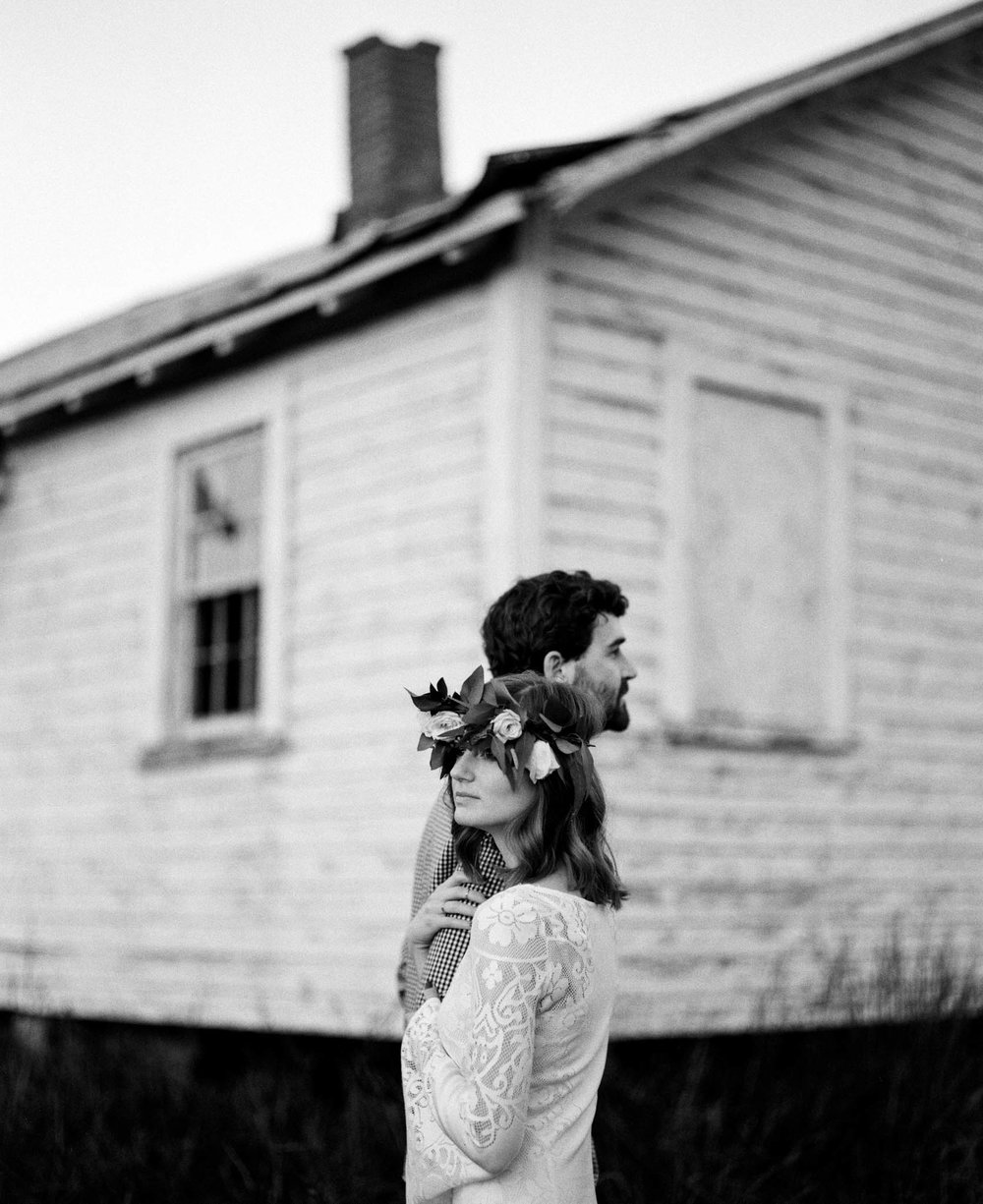 Heather and Trevor holding one another in front of an old farmhouse, Chapel Hill, NC