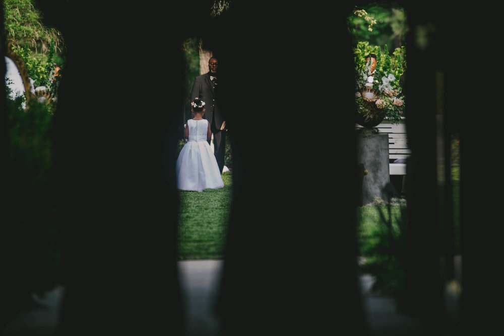 A flower girl as seen between the shadows of the two grandmothers during the processional of the wedding