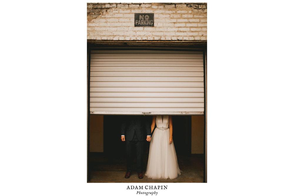 bride and groom hidden behind half a loading dock door