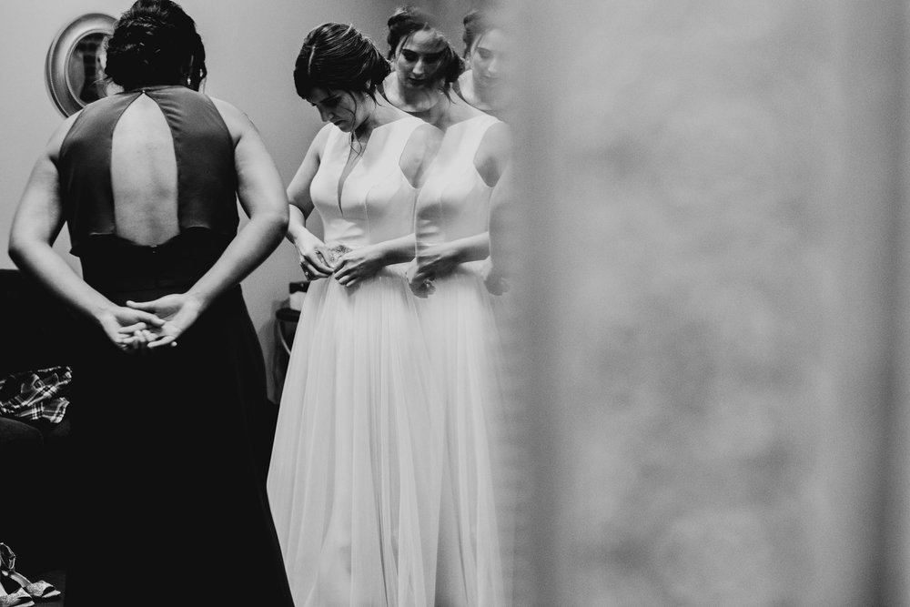 bride and bridesmaid checking out dress