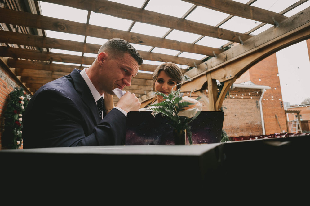 groom crying while watching special video made for him by the bride