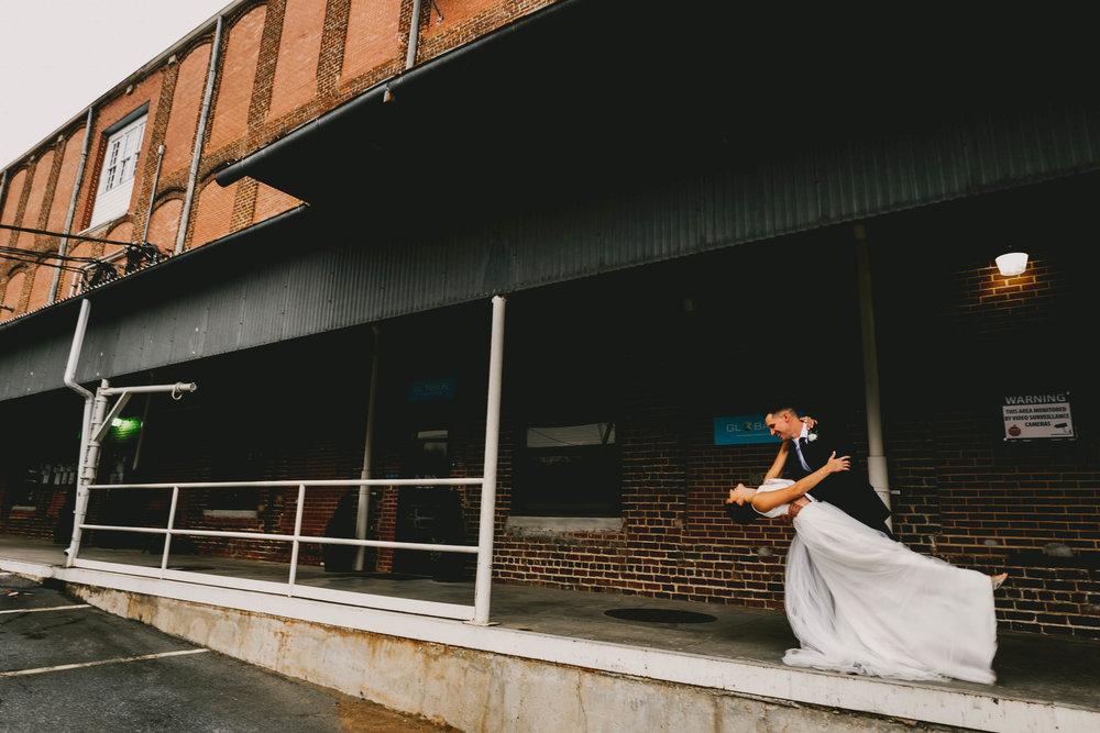 groom dips bride while dancing on loading dock