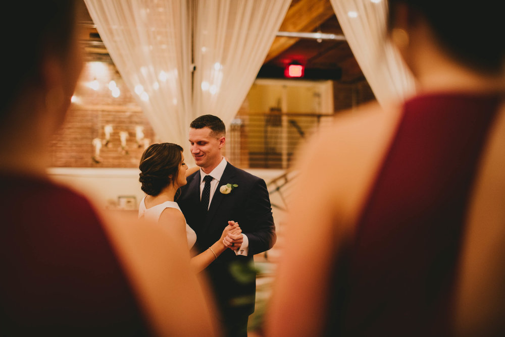 bride and groom share their first dance as seen between two bridesmaids