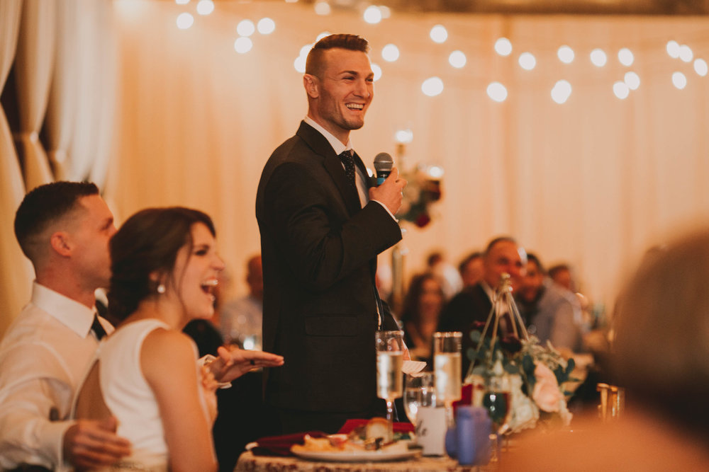 best man sharing toast to the bride and groom