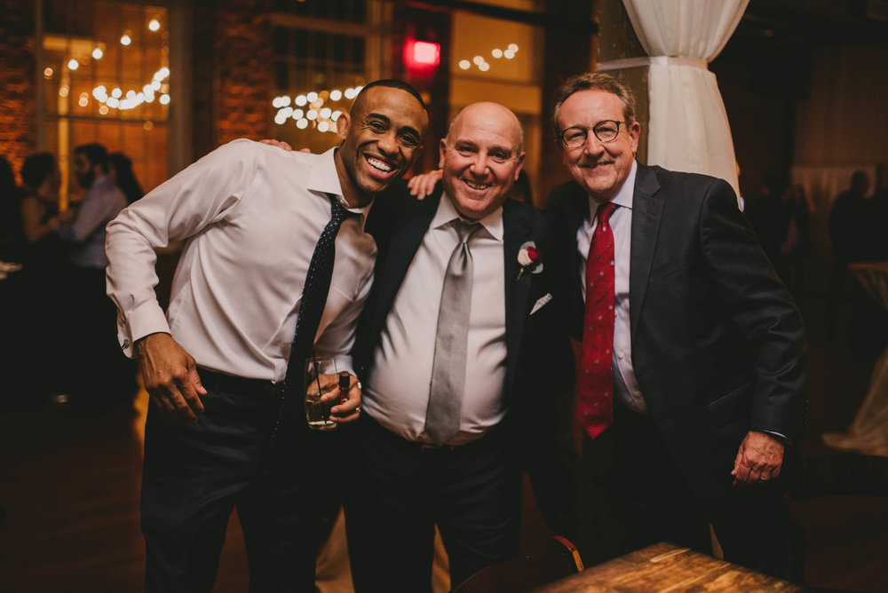 a groomsmen and the father of the bride and a wedding guest during the reception