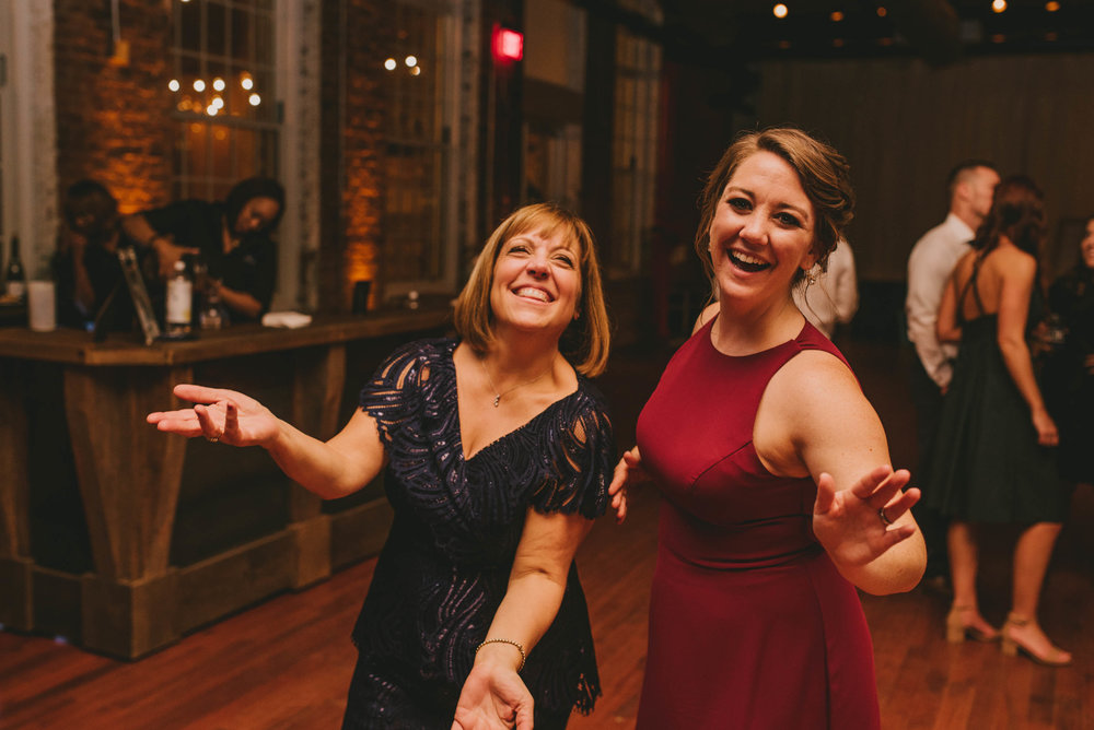 mother of the bride and daughter in law dancing and laughing during reception