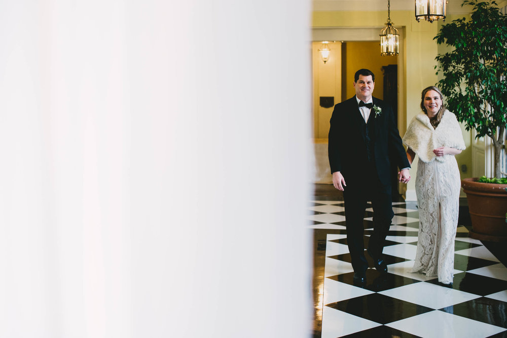 the bride and groom walking down the classic black and white tiles Carolina Inn hallway