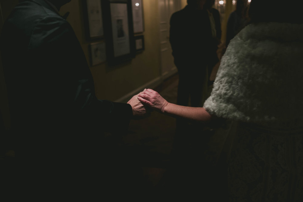the bride and groom holding hands in a dimly lit hallway of the Carolina Inn