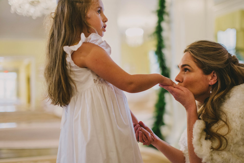 the bride kissing her daughters hand before the ceremony