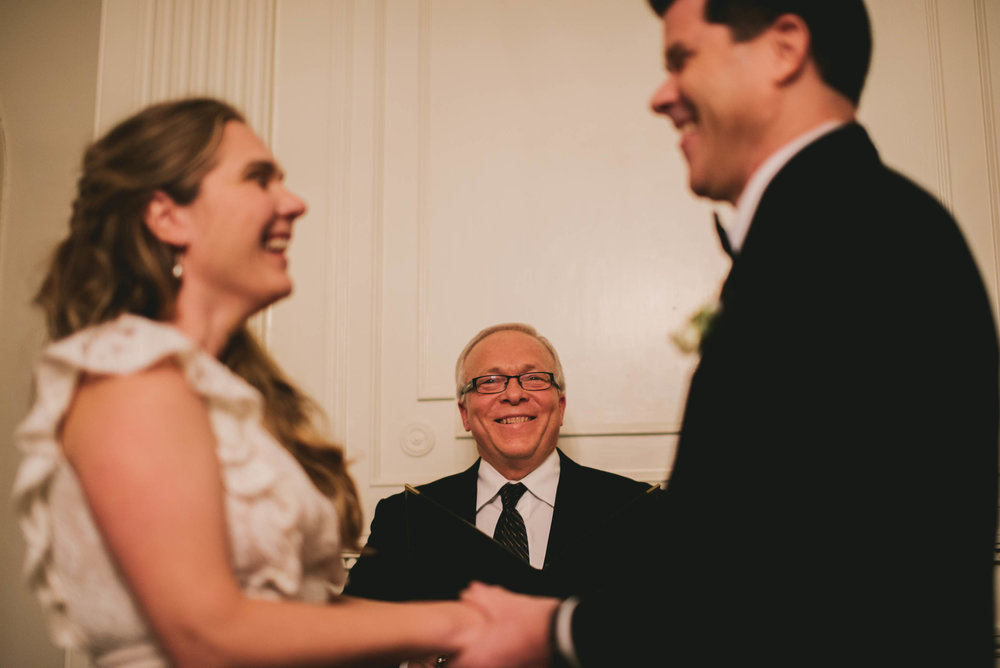 the bride, groom and officiant laughing during this Carolina Inn wedding ceremony